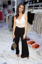 Emily Ratajkowski styled her look with an elegant beaded purse.