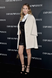 Dylan Penn hit the Emporio Armani fashion show wearing a cream-colored pea coat over black leather shortalls.