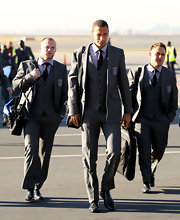 Wayne and his team wear matching gray suits with classically English buttoned vests underneath.