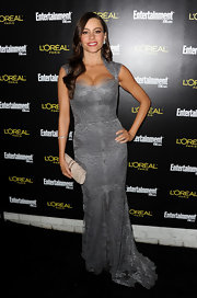 Sofia Vergara complemented her stunning gray gown with a cream snakeskin envelope clutch with gold accents.