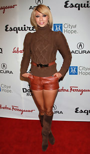 Keri wears a thick cable turtle neck sweater with tiny leather shorts.