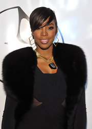 Kelly Rowland added a nice touch to her elegant black dress with a gold and black pendant necklace.