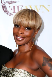 Mry J. Blige has a cross with a rose in the middle tattooed on her left bicep.