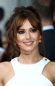 Cheryl Cole added dark neutrals, smoky metallic shades of shadow and rich black mascara to create her sexy makeup look.