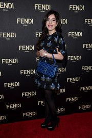 Paola Fendi accessorized with a studded blue purse, also by Fendi.
