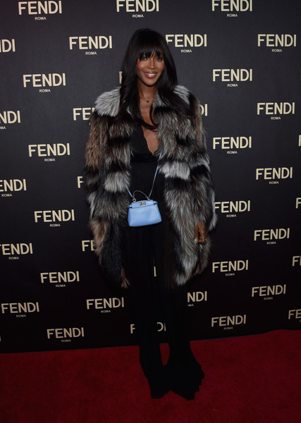 Naomi Campbell added a pop of pastel to her dark outfit with a mini blue Fendi bag.