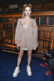 Chiara Ferragni layered a baggy beige hoodie over a lacy dress, both by Fenty x Puma, for the brand's fashion show.