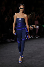 Joan Smalls was sporty-sexy in a strapless, harness-embellished navy catsuit on the Fenty Puma Spring 2018 runway.