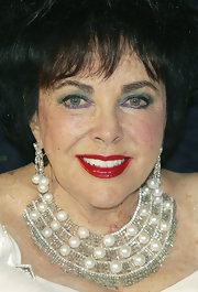 Elizabeth Taylor glammed it up with a pair of diamond and pearl dangling earrings and a matching collar necklace.