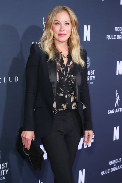 Christina Applegate teamed a black envelope clutch with a pantsuit and print blouse for the Rebels and Rule Breakers event.