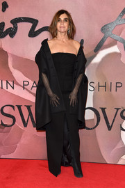 Carine Roitfeld wore a black cape coat over her gown for added elegance.