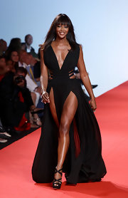 Naomi Campbell flaunted her toned legs in a pair of black double crisscross platform sandals.