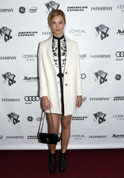 Karlie Kloss styled her look with an elegant black chain-strap bag by Alexander McQueen.