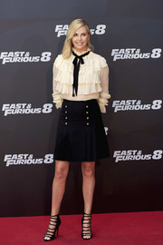A pleated black mini skirt with gold buttons (also by Gucci) completed Charlize Theron's outfit.