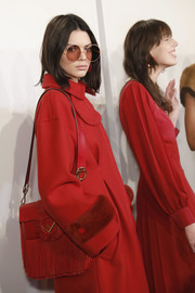 Kendall Jenner waited backstage during the Fendi runway show carrying a fringed red shoulder bag.