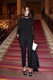 Carine Roitfeld teamed her blouse with a pair of black cigarette pants.
