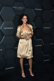 Rihanna was classic and chic in a gold trenchcoat by Burberry during her Fenty Beauty talk.