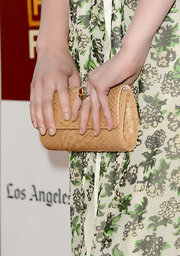 Greta Gerwig complemented her vibrant dress with a classic nude snakeskin clutch when she attended the premiere of 'To Rome with Love.'
