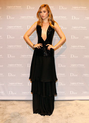 Suki Waterhouse sure loves a deep plunge! For the Fine Arts Museums of San Francisco Mid-Winter Gala, she chose a super-sultry black Dior gown with a down-to-the-navel neckline and an elegant tiered skirt.