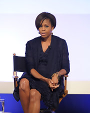 Michelle Obama oozed ultra-feminine sophistication in a navy ruffle dress with matching cardigan during an event at the Writers Guild Theater.