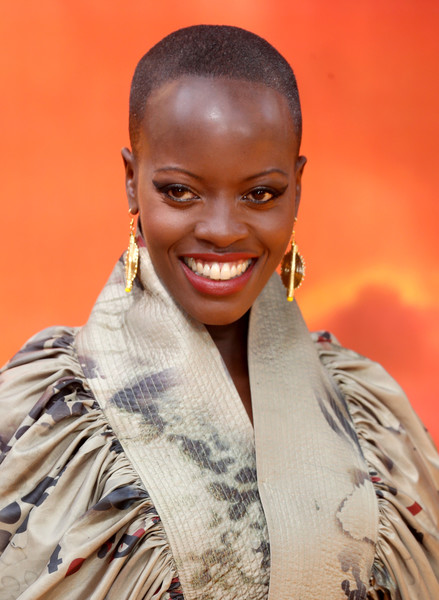 Florence Kasumba Buzzcut [the lion king,hair,face,facial expression,beauty,hairstyle,head,smile,fashion,lip,lady,european premiere,florence kasumba,european,england,london,leicester square,red carpet arrivals,premiere]