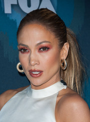 Jennifer Lopez got stagy on the beauty front, sporting a too-heavy application of coral eyeshadow.