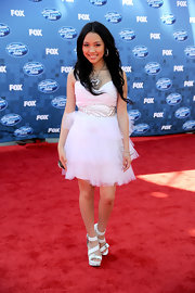 Thia Megia balanced her flouncy white tulle dress with strappy buckled platforms.