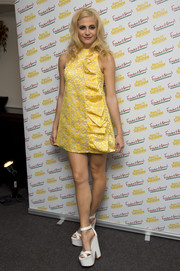 Pixie Lott was in a '60s mood during the Rays of Sunshine concert, wearing this ruffled yellow A-line mini dress by A.W.A.K.E.