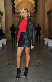 Alesha Dixon was all legs in a black leather mini, which she teamed with a matching jacket and a red sweater, at the Topshop Unique fashion show.