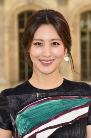Claudia Kim pulled her tresses back into a loose ponytail for the Christian Dior fashion show.