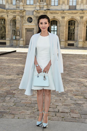 Continuing the pale-blue theme, Li Bingbing accessorized with a stylish Dior leather purse.