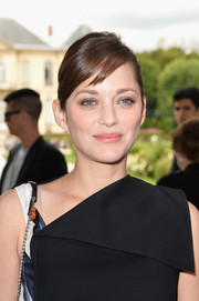 Marion Cotillard attended the Dior Couture show wearing her hair in a simple bun with side-swept bangs.