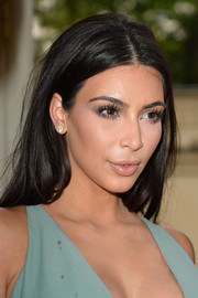 Kim Kardashian played down her kissers with some nude lipstick.