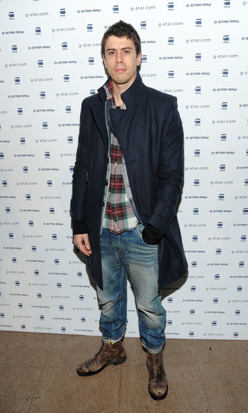 Toby finishes his jeans and plaid shirt look with rugged boots and a navy wool overcoat—rather dashing, no?
