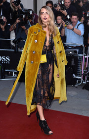 Cara Delevingne toned down the sexiness of her see-through dress with a mustard fur trenchcoat by Burberry Prorsum as she arrived for the GQ Men of the Year Awards.