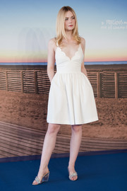 Elle Fanning styled her dress with a pair of bejeweled PVC wedges.