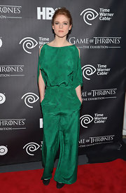 Rose Leslie chose an emerald green jumpsuit with wide legs and shoulder cutouts for her sleek and sophisticated red carpet look.