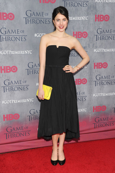 Margaret Qualley added a splash of color to her black outfit with a yellow leather clutch.