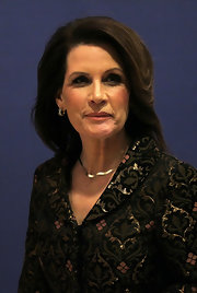 Michele wore her hair swept back in a loose wave with her collared brocade jacket.