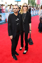 Barbara Bach matched her husband's style with a sophisticated black pantsuit and printed shirt.