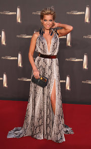 Sylvie van der Vaart completed her red carpet look with a fashionable black and gold gemstone inlaid clutch.