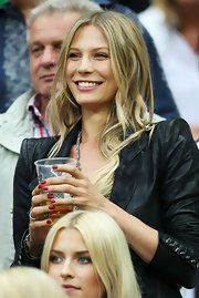 Sarah Brandner wore her hair in a summery center-parted wavy style while watching a football match.