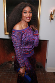 Angela Bassett's electric-blue Ethan K croc-embossed clutch made a striking contrast to her purple outfit at the Gersh Oscar party.