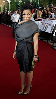 Janet looked stunning in a draped gray dress with bronze accessories. The actress completed her look with metallic pumps.