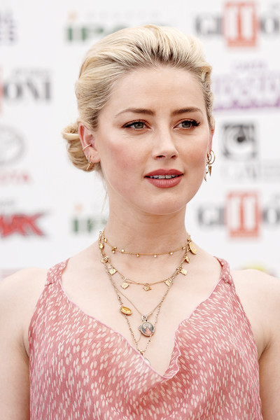 Amber Heard adorned her low neckline with layers of gold necklaces.