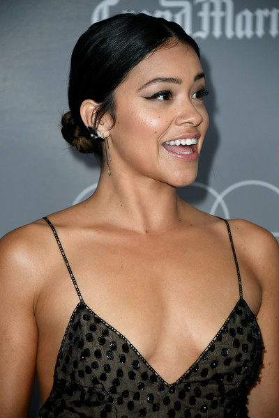 Gina Rodriguez Twisted Bun [hair,beauty,fashion model,hairstyle,human hair color,eyebrow,chin,lady,shoulder,smile,arrivals,gina rodriguez,costume designers guild awards,beverly hills,california,the beverly hilton hotel,cdga]