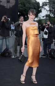 Milla Jovovich wore a silk orange gown that featured a spaghetti strap halter neck.