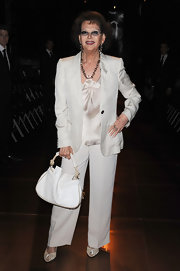 Claudia paired her white pant suit with a white leather hobo bag.