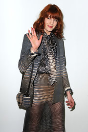 Florence wears a geometric print tie-neck blouse with a matching skirt and blazer for the Givenchy fashion show.