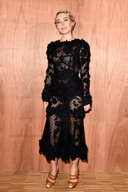 Ulyana Sergeenko put on a daring display in a sheer black dress during the Givenchy fashion show.